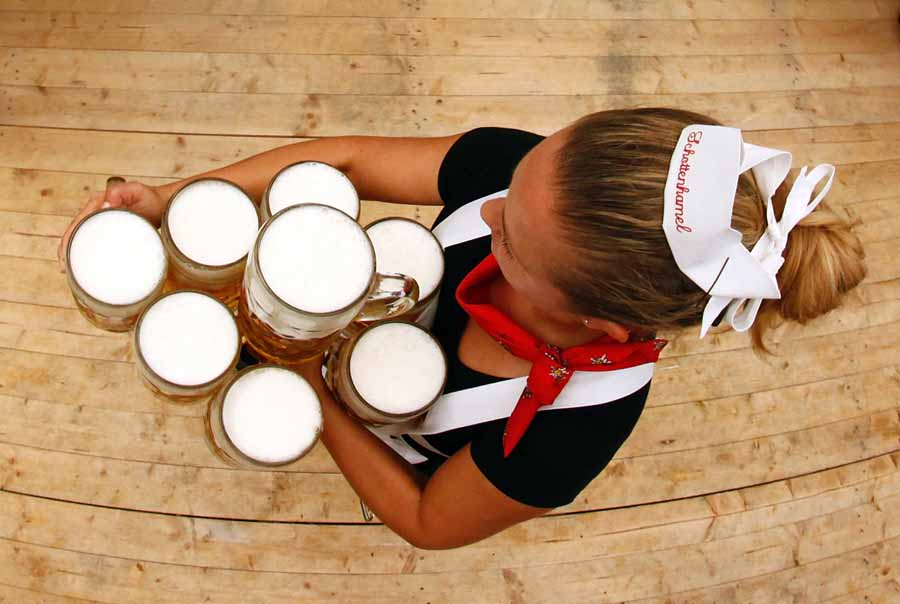 A waitress carries the traditional 1-litre beer mugs at the opening of the Munich Oktoberfest
